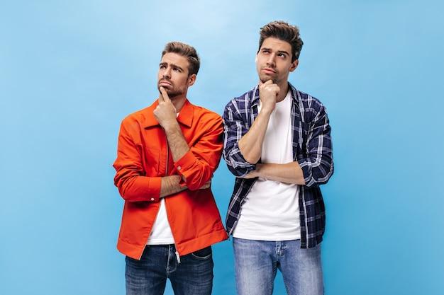 Nachdenkliche junge männer in weißen t-shirts und stylischen hemden blicken auf. mann in orangefarbener jacke und mann in kariertem hemd posieren an blauer wand.
