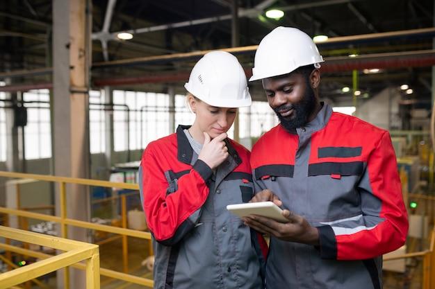 Nachdenkliche junge multiethnische arbeiter in helmen, die tablets verwenden, während sie industrielle produktionsdaten analysieren