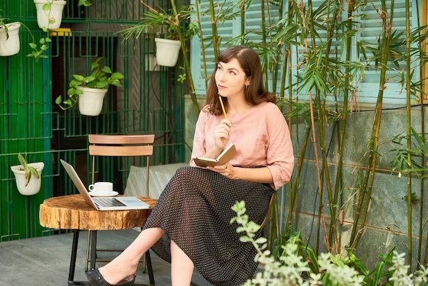 Nachdenkliche junge schriftstellerin, die beim kaffeetrinken im hinterhof ihres hauses über ideen für ein neues buch nachdenkt