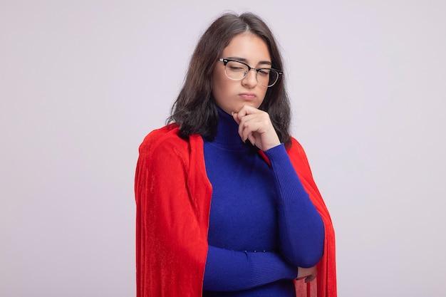Nachdenkliche junge superheldin in rotem umhang mit brille, die die hand am kinn hält und nach unten schaut, isoliert auf weiße wand mit kopierraum