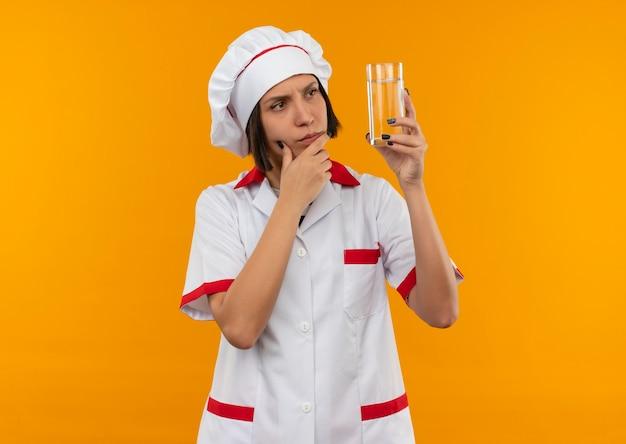 Nachdenkliche junge weibliche köchin in der kochuniform, die das glas wasser mit der hand am kinn hält und auf orange wand lokalisiert hält