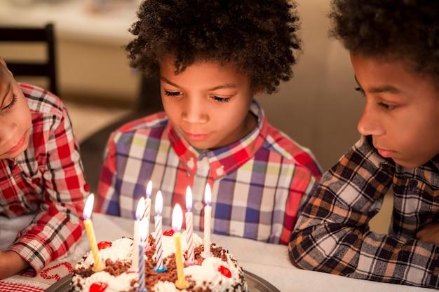 Nachdenkliche jungs in der nähe von geburtstagskuchen afro kinder kleine geburtstagsfeier finden frieden in sich selbst werden ...