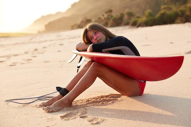 Nachdenkliche kaukasische frau im badeanzug, verwendet leine zum surfen longboard, lehnt an händen