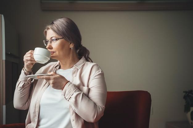 Nachdenkliche kaukasische frau mit den blonden haaren, die einen kaffee nahe dem fenster trinken