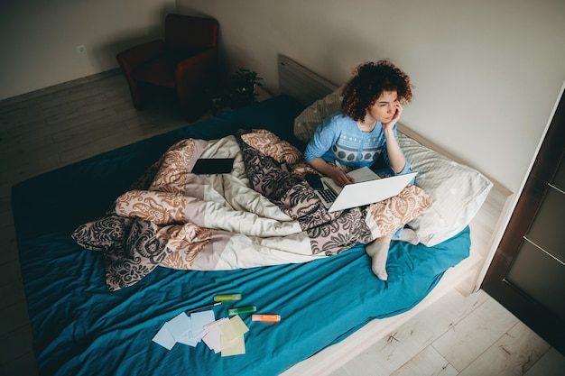 Nachdenkliche kaukasische geschäftsdame mit dem lockigen haar, das auf dem sofa mit einem laptop sitzt, der einige notizen im buch macht