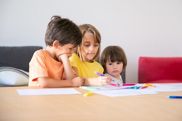 Nachdenkliche kinder malen mit markern im wohnzimmer. drei kaukasische entzückende kinder, die zusammen sitzen, das leben genießen, zeichnen und zusammen spielen. kindheit, kreativität und wochenendkonzept
