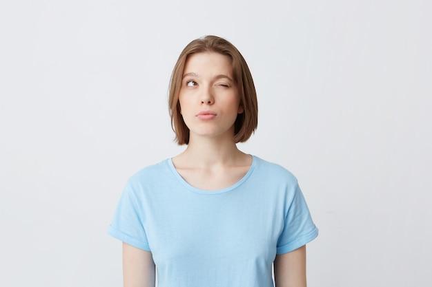 Nachdenkliche konzentrierte junge frau im blauen t-shirt mit einem geschlossenen auge, das denkt und versucht, sich an antworten zu erinnern
