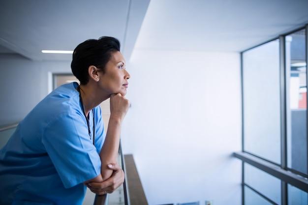 Nachdenkliche krankenschwester, die sich auf geländer im korridor stützt