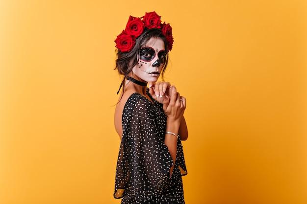 Nachdenkliche latina, die auf mysteriöse weise auf isolierter orange wand aufwirft. dame mit gesicht für halloween gemalt berührt sich