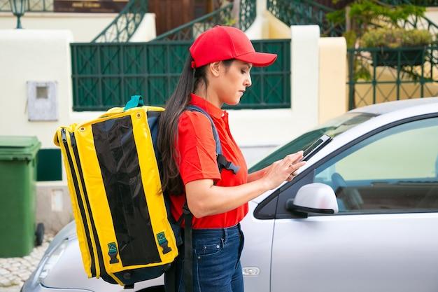 Nachdenkliche lieferfrau beobachtet erforderliches haus auf tablette. junger weiblicher kurier mit gelbem thermorucksack, der expressauftrag liefert und auf straße geht. lieferservice und online-shopping-konzept