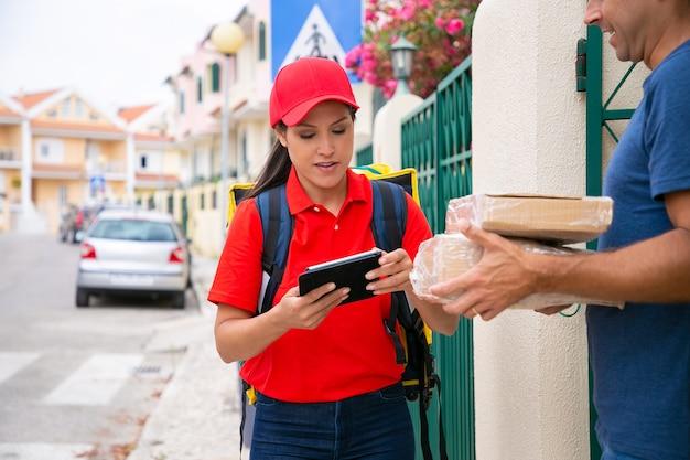 Nachdenkliche lieferfrau in roter uniform prüft daten auf tablett und spricht. beschnittener mann mittleren alters, der bestellung erhält, pappkartons hält und auf der straße steht. lieferservice und postkonzept
