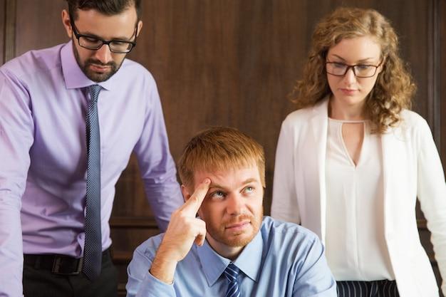 Nachdenkliche mann mit den fingern auf der stirn, während seine beiden begleiter ihn beobachten