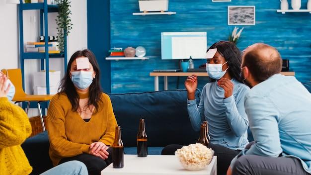 Nachdenkliche multiethnische freunde mit haftnotizen auf der stirn, die ein namensspiel mit gesichtsmaske spielen, um soziale distanzierung aufrechtzuerhalten, um zu verhindern, dass sich covid19 ausbreitet, bier trinken und popcorn genießen