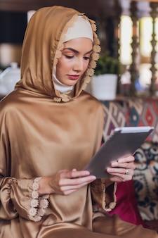 Nachdenkliche muslimische frau, die digitales tablett betrachtet