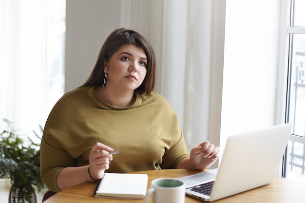 Nachdenkliche nachdenkliche junge mollige journalistin, die am schreibtisch mit tragbarem computer, becher sitzt, aufschaut, während notizen im heft macht, entfernt arbeitet, neuen artikel für online-magazin schreibt