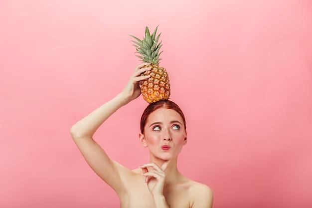 Nachdenkliche nackte frau, die ananas hält. ingwer kaukasisches mädchen mit exotischen früchten und wegschauen.