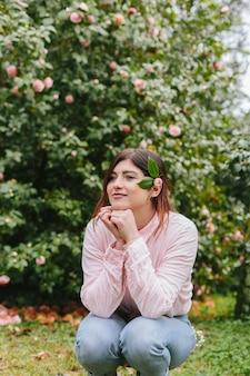 Nachdenkliche positive frau mit anlage im haar nahe den rosa blumen, die auf grünen zweigen wachsen