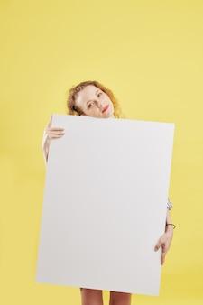 Nachdenkliche positive frau mit papierplakat