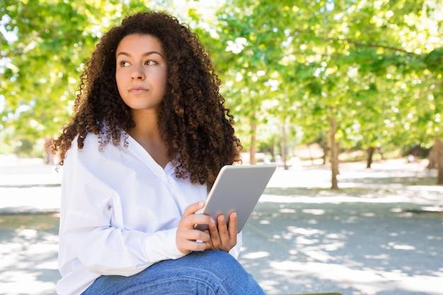 Nachdenkliche recht junge frau, die tablette auf bank im park verwendet