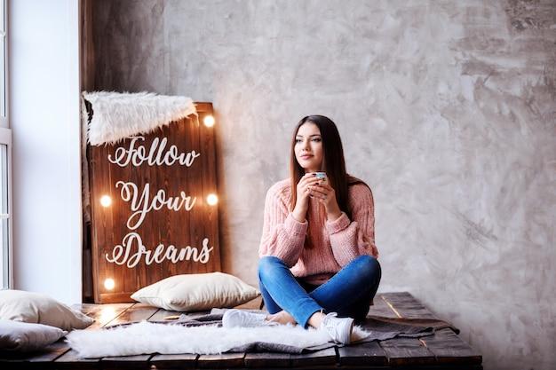 Nachdenkliche romantische frau sitzt mit gekreuzten beinen und einer tasse kaffee in ihren händen. gut aussehendes mädchen sitzt vor lichtpaneel mit schriftzug follow your dreams und grauer wand. raum.