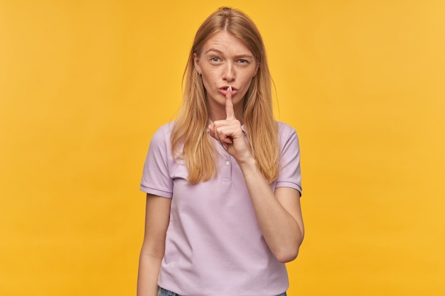 Nachdenkliche schöne frau mit sommersprossen im lavendel-t-shirt halten die stirn hoch und zeigen schweigegeste auf gelb