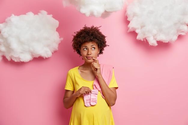 Nachdenkliche schwangere frau mit lockigem haar denkt an zukünftige mutterschaft hält socken über bauch konzentriert irgendwo konzentriert nachdenklich gekleidet lässig hat großen bauch