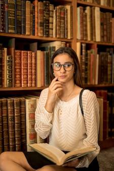 Nachdenkliche studentin, die mit buch in der bibliothek sitzt