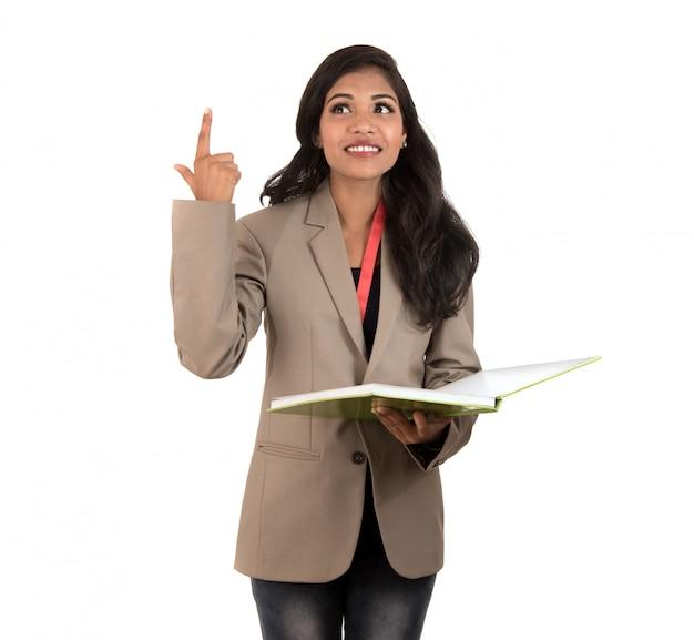Nachdenkliche studentin, lehrerin oder geschäftsdame, die bücher hält und ok zeichen auf leerraum zeigt