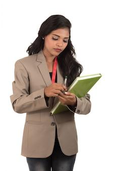 Nachdenkliche studentin, lehrerin oder geschäftsfrau, die bücher hält. auf weißen flächen isoliert