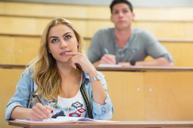 Nachdenkliche studentin während des unterrichts im hörsaal