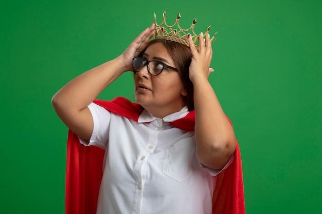 Nachdenkliche superheldenfrau mittleren alters, die nach oben schaut und krone auf kopf lokalisiert auf grün setzt