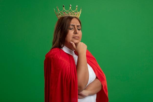 Nachdenkliche superheldenfrau mittleren alters, die nach unten schaut und die krone trägt, packte das kinn isoliert auf grün