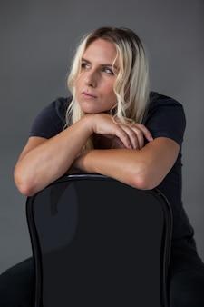 Nachdenkliche transgender-frau, die sich auf stuhl stützt