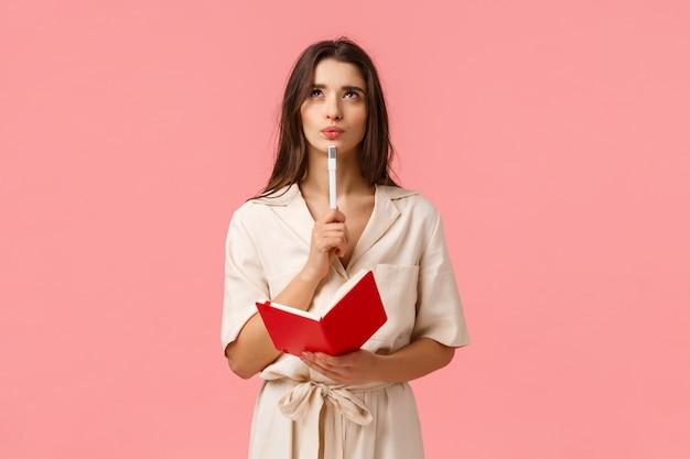 Nachdenkliche und kreative junge frau, die liste macht, schmollt und nachdenklich und inspiriert nachschaut, rotes notizbuch und stift hält, neues gedicht erstellt oder sich auf die prüfung vorbereitet, über rosa wand nachdenkend