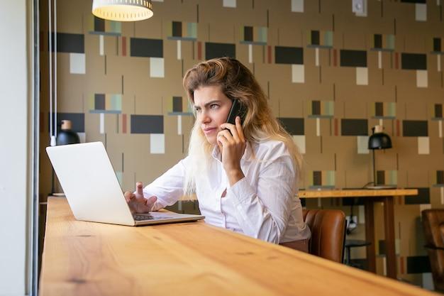 Nachdenkliche unternehmerin, die laptop verwendet und auf mobiltelefon im gemeinsamen arbeitsraum spricht