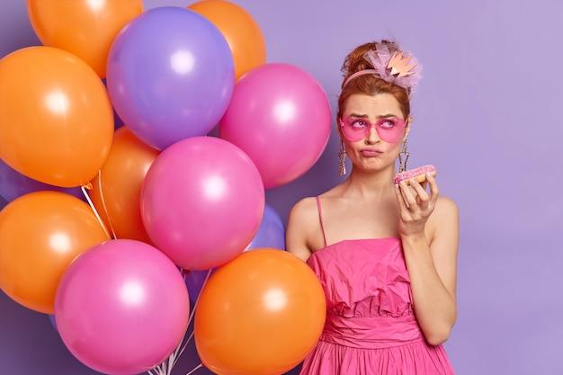 Nachdenkliche unzufriedene schöne frau fühlt sich gelangweilt auf urlaubsparty wartet lange auf den anfang hält süßen donut und bündel mehrfarbiger luftballons
