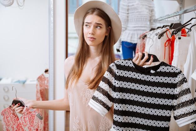 Nachdenkliche verwirrte junge frau, die zwischen zwei kleidern im bekleidungsgeschäft wählt