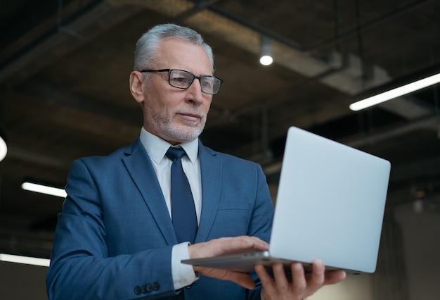 Nachdenklicher älterer geschäftsmann, der laptop benutzt, tippt, online sucht, nachrichten im büro liest