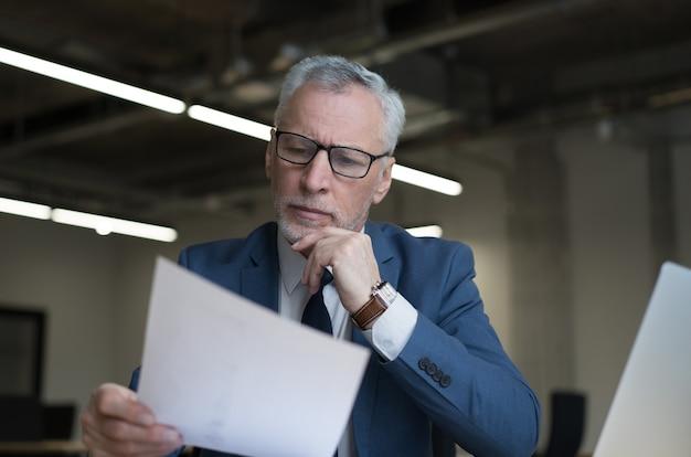 Nachdenklicher älterer geschäftsmann, der vertrag liest, der im modernen büro arbeitet