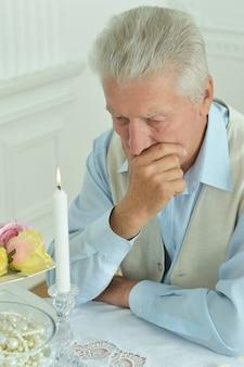 Nachdenklicher älterer mann, der auf dem tisch sitzt
