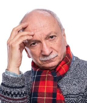 Nachdenklicher älterer mann, der im studio über weißem hintergrund aufwirft