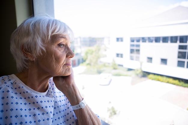 Nachdenklicher älterer patient, der durch fenster schaut