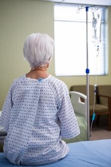 Nachdenklicher älterer patient, der im krankenhaus sitzt
