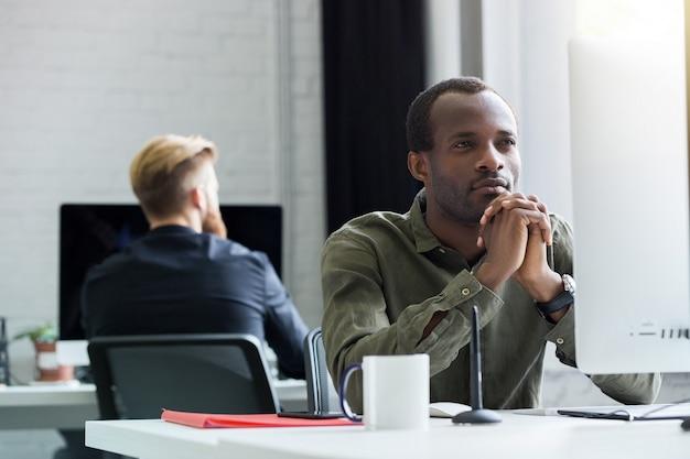 Nachdenklicher afrikanischer mann, der an seinem schreibtisch sitzt