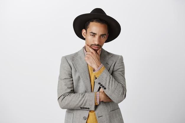 Nachdenklicher afroamerikaner im anzug, der entscheidung trifft, kinn berührt und schaut, über wahl nachdenkt