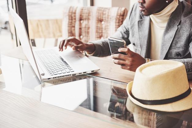 Nachdenklicher afroamerikanischer hübscher berufsverfasser von populären artikeln im blog kleidete in der modischen ausstattung und in den gläsern an, die über der neuen geschichte denken, die sein skript vom notizbuch korrektur liest, das im café sitzt