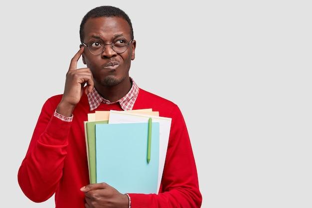 Nachdenklicher afroamerikanischer mann spitzt lippen berührt schläfe, denkt über etwas nach, trägt ordner mit stift