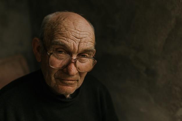 Nachdenklicher alter mann in brille mit grauem haar schaut weg.