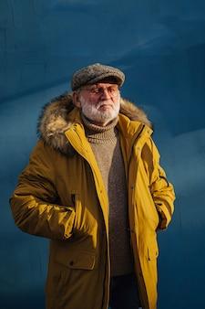 Nachdenklicher alter mann in stylischer oberbekleidung, der die hände in den taschen hält