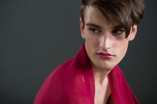 Nachdenklicher androgyner mann in roten kleidern